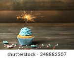Cupcake with sparkler on table...