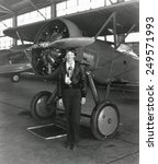 Small photo of Amelia Earhart standing next to an airplane, July 30, 1936.