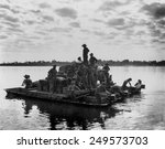 U.S. Army barge, powered by outboard motors, on the Irrawaddy River near Tigyiang, Burma. The soldiers were transporting a truck and ammunition during World War 2, Dec. 30, 1944.