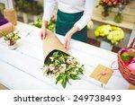 female florist selling bouquet... | Shutterstock . vector #249738493