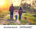 Stock photo happy family with dog walking in the village at sunset back to camera 249964087