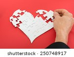 Small photo of Close-up Of A Person's Hand Solving Heartshape Jigsaw Puzzle