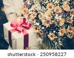 Gift Box And Flowers In Hands...