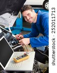 mechanic using laptop on car at ... | Shutterstock . vector #252011713
