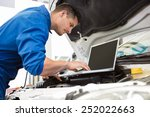 mechanic using laptop on car at ... | Shutterstock . vector #252022663