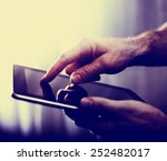 hands typing on a tablet toned... | Shutterstock . vector #252482017