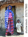 Small photo of Meserani Snake Park, Arusha, Tanzania - February 14, 2008: Young woman Maasai tribe in draped robe, and a little girl standing in front of his house, small huts made of mud and cow dung.
