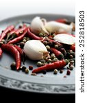 Small photo of Bird Eye Chillies and garlic cloves scattered on a pewter plate with peppercorns with a shallow depth of field. Copy space.
