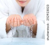 Small photo of Young woman washing face with clean water