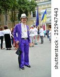 Small photo of KIEV, UKRAINE - AUGUST 24: Some racy man in embroided shirt a purple suit with hat and umbrella posing for photo at All Ukrainian Vyshyvanka Parade at Independence Day on August 24, 2013