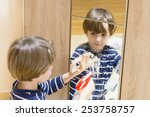 cute boy cleaning the mirror... | Shutterstock . vector #253758757