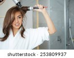 Young Woman Blow Drying Hair I...