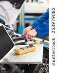mechanic using laptop on car at ... | Shutterstock . vector #253979083