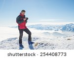 Small photo of Alpinist with phone in hand on the summit with majestic panoramic view of the italian Alps in winter season. Concept of sharing life moments using new technology even in hard condition.