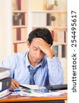 Small photo of young stressed overwhelmed business man with piles of folders on his desk