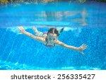 happy girl swims in pool... | Shutterstock . vector #256335427