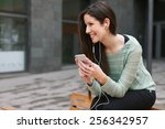 young woman sitting on a bench... | Shutterstock . vector #256342957