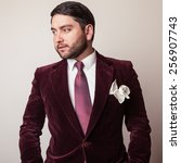 Small photo of Elegant young handsome man in luxury velvet claret costume. Studio fashion portrait.