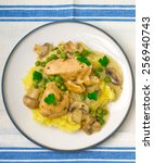 Small photo of fricassee from chicken with vegetables and mashed potatoes on a white plate. top view. selective focus.