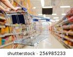 Woman Pushing Shopping Cart In...