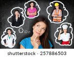 Small photo of Education and career choice options - student thinking of future. Young Asian woman contemplating career options smiling looking up at thought bubbles on a blackboard with different professions