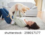 happy young woman lifting puppy ... | Shutterstock . vector #258017177