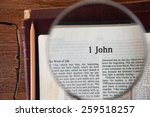 "Small photo of CHIANGMAI, THAILAND, March 3,2015. Reading The New International Version of the Holy Bible on the page of "" 1 john "" at home. March 3,2015"