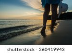 Woman Walking On The Beach At...