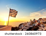 Small photo of Greek flag waving at sunset in Oia, Santorini, Greece