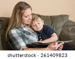 a young boy snuggles into his... | Shutterstock . vector #261409823