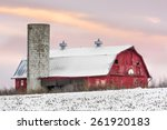 A Snowy Red Barn With Silo And...