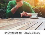 Small photo of Cropped image male freelancer sitting at the table with cup of coffee, digital tablet and smart phone, man's hands typing message on touch screen tablet while sitting on balcony terrace, flare sun