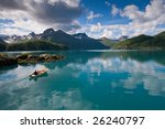 Small boat with two persons on Norwegian fjord - stock photo
