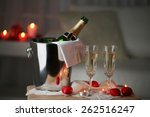 Stock photo champagne glasses and rose petals for celebrating valentines day on dark background 262516247