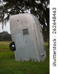 Small photo of DOVER, FLORIDA,USA-JANUARY 15: Trailers are buried nose first at the Airstream Ranch in Dover on January 15, 2015. Airstream Ranch is a set of old travel trailers buried in the ground.