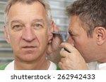 Small photo of Mature man at medical examination, otoscopy