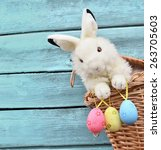Small photo of Happy Easter Bunny in a basket and eggs on a blue wooden background.