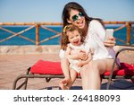Small photo of Little girl and her mom having some fun at the beach and taking a selfie with a smartphone