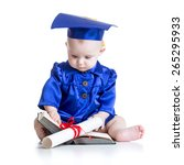Small photo of Portrait of cute baby boy in academic costume with book and scroll