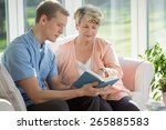 Small photo of Male senior care assistant caring about elderly woman