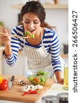 young woman eating fresh salad... | Shutterstock . vector #266506427