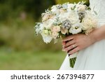 Stock photo beautiful tender wedding bouquet of cream roses and eustoma flowers in hands of the bride 267394877
