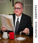 Small photo of Humorous scene of a business man dressed in a suit and tie sitting down to morning coffee reading the newspaper and absentmindedly missing the cup as he adds sugar to his coffee.