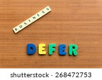 Small photo of defer colorful word on the wooden background