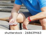 Small photo of Sportive man sits on a bench and checks his fitness results on a smart phone. He wears a fitness tracker wristband on his left arm.