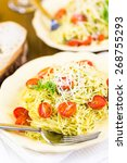 Small photo of Homemade angel hair pasta with pesto sauce and roasted cherry tomatoes.