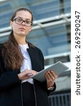 Small photo of Business confidence. Portrait of motivated business woman. Girl is standing with tablet. She is waiting for her business parter. Outdoors business concept