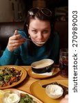 the woman eating soup in the... | Shutterstock . vector #270989003
