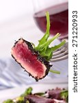 Small photo of Seared ahi tuna coated sesame seeds on fork