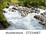Fast flowing river in the alps - stock photo